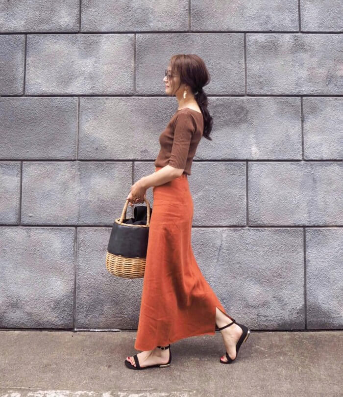 テラコッタカラーのスリットロングスカートとブラウントップスのコーデ画像