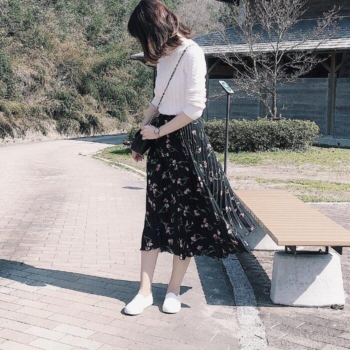 白ニット×黒花柄プリーツスカートのコーデ画像