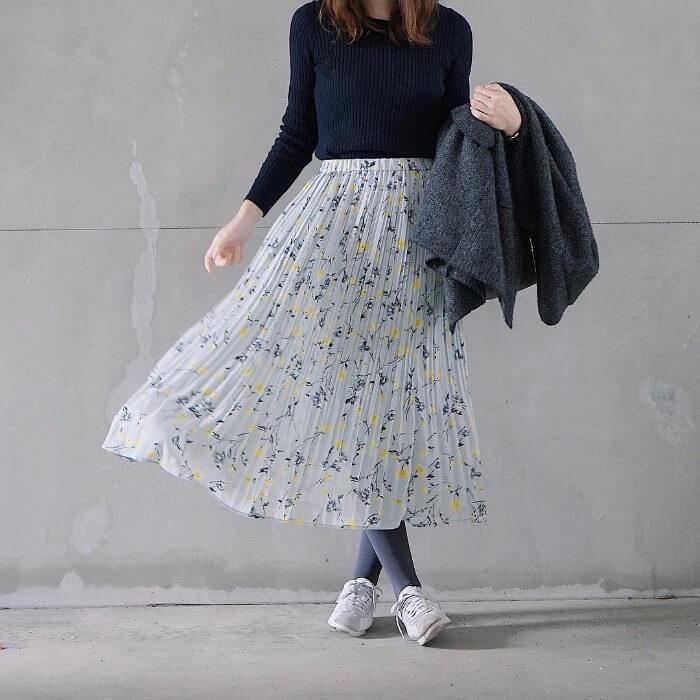 黒リブニット×淡水色花柄プリーツスカートのコーデ画像
