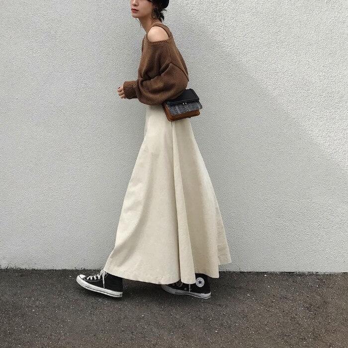 ブラウンニットと白マキシフレアスカートとスニーカーのコーデ画像