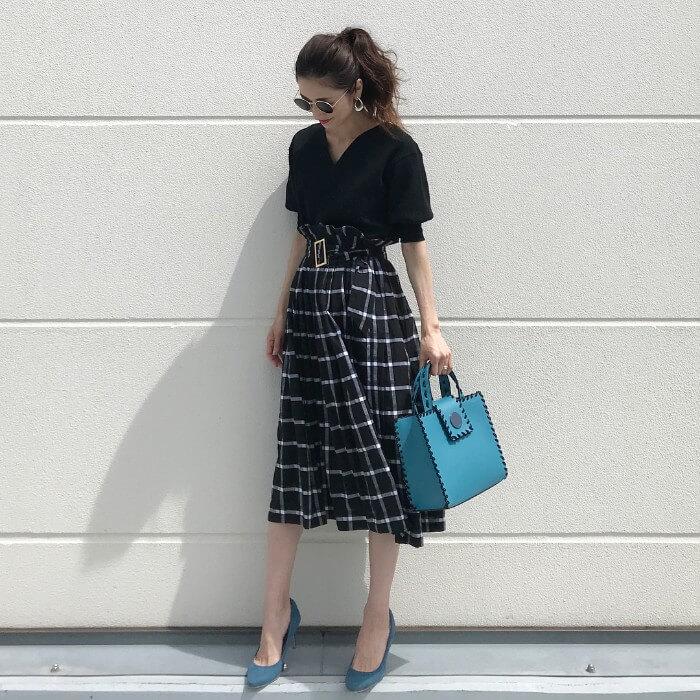 チェック柄スカートと黒トップスに水色小物のコーデ画像