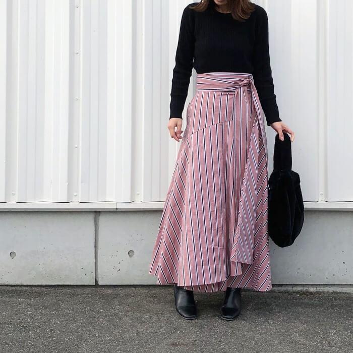 ピンクベースのストライプスカートと黒トップスのコーデ画像