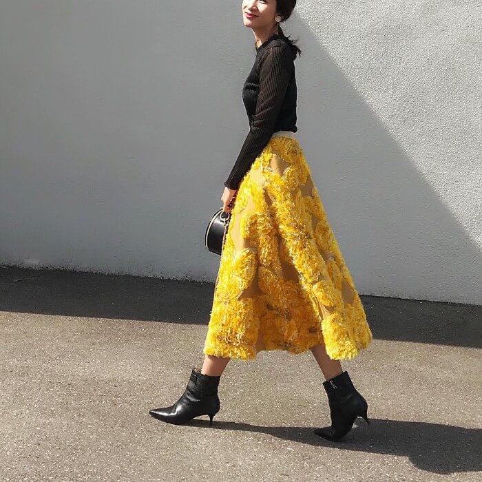 黒ニット×からし色花柄スカートのコーデ画像