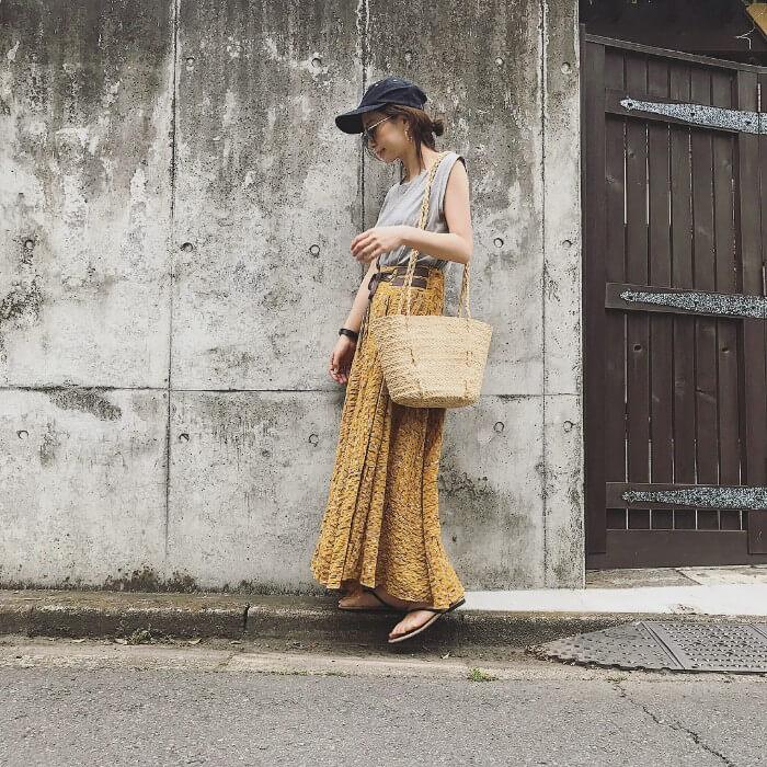 黒キャップ×グレーノースリーブ×黄ロングスカートの春夏コーデ画像