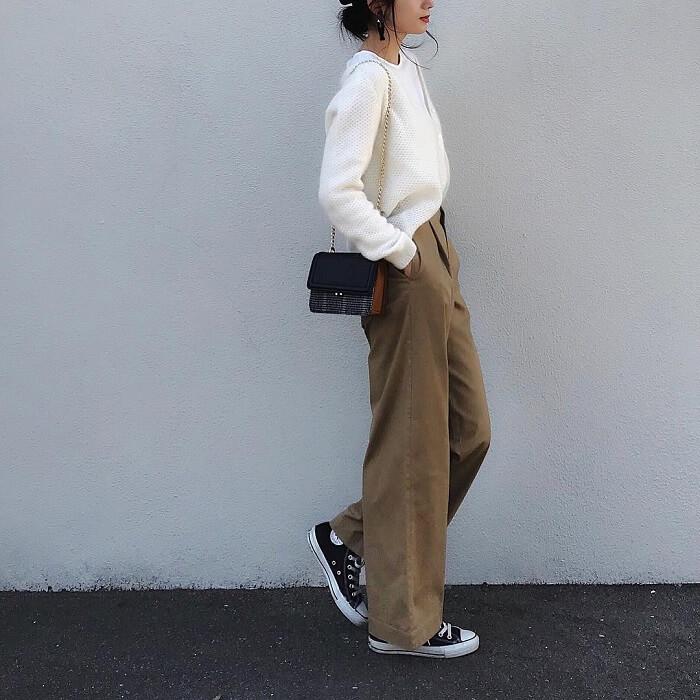 チノ素材の茶色ワイドパンツに白黒のコンバーススニーカーを組み合わせたコーデ写真
