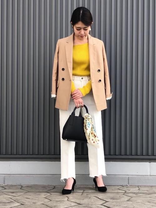 ベージュのジャケットとマスタード色のニットのコーデ画像