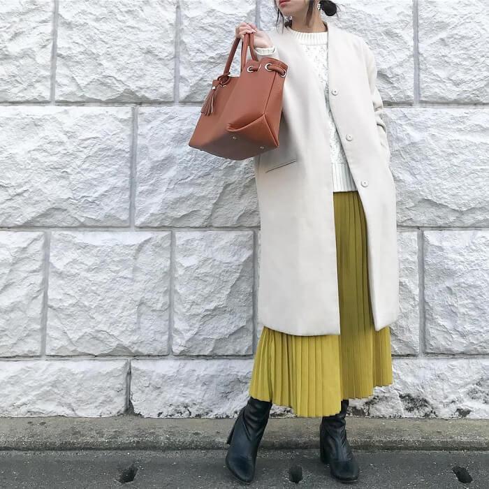 イエロープリーツスカート×ホワイトノーカラーコートのコーデ画像