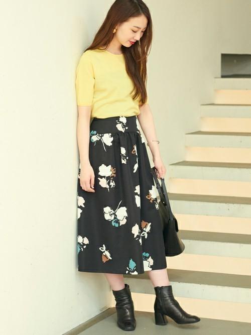 イエローニットと黒の大花柄スカートのコーデ画像