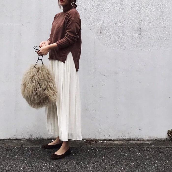 ブラウンタートルニット×白プリーツスカートのコーデ画像