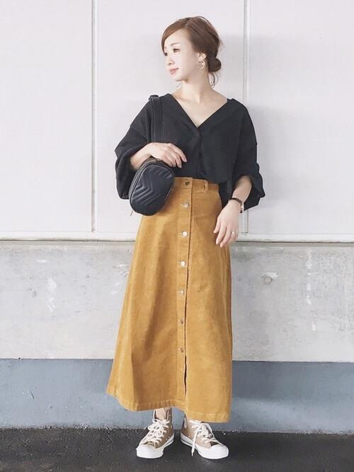 黄みベージュコーデュロイスカートと黒ブラウスのコーデ画像