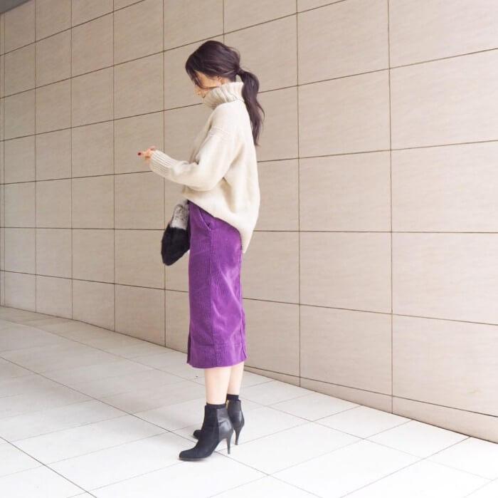 パープルのコーデュロイスカートと白ニットのコーデ画像