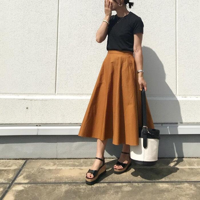 黒の無地tシャツとキャメルサーキュラースカートのコーデ画像