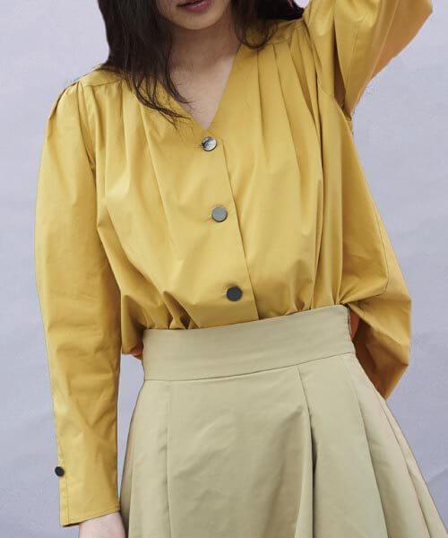 イエローVネックシャツ×ベージュフレアスカートのコーデ画像