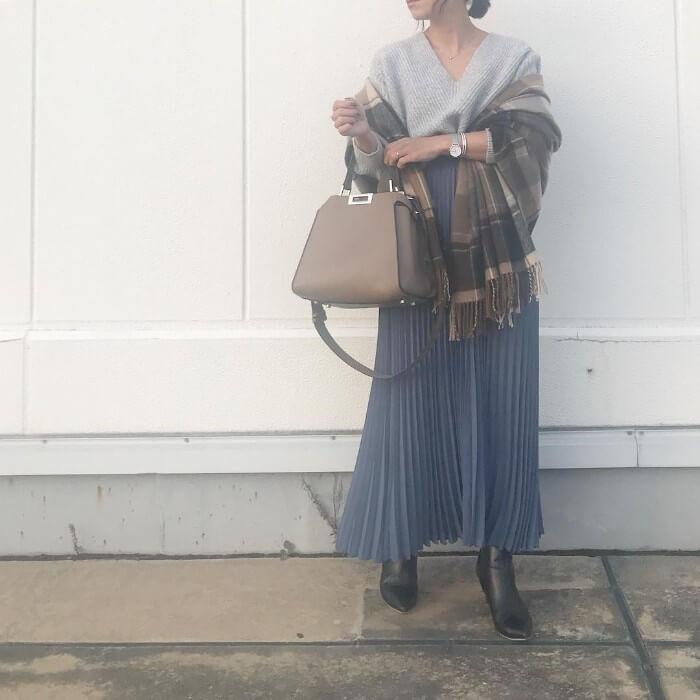 グレーのVネックニットとネイビーのロングスカートのコーデ画像