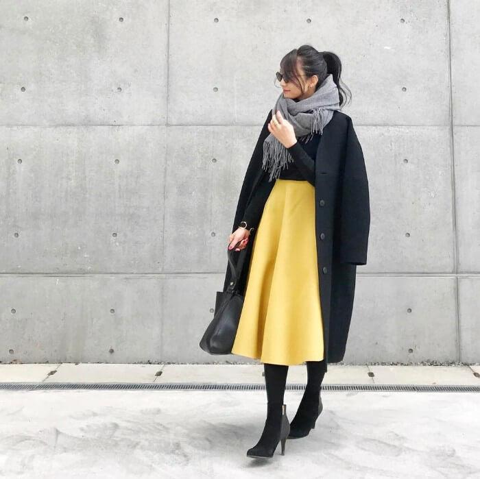 レモン色スカートとロングコートマフラーのコーデ画像