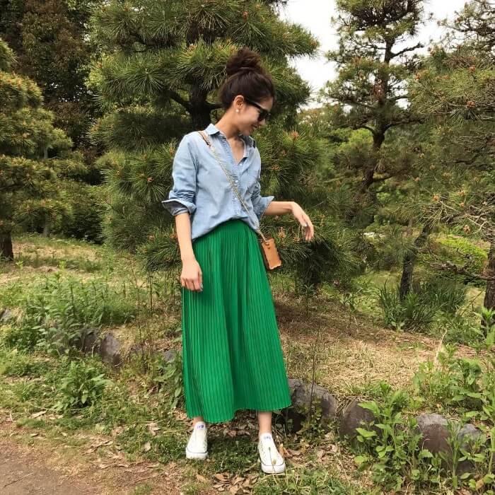 水色シャツ×グリーンプリーツスカート×白スニーカーのコーデ画像