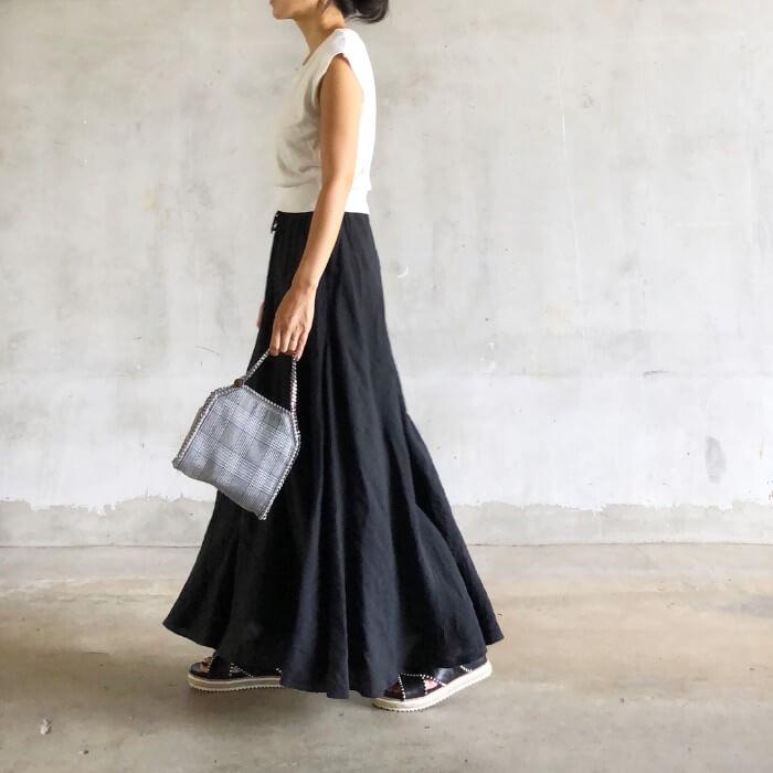 白ノースリーブニット×黒マキシフレアスカートのコーデ画像