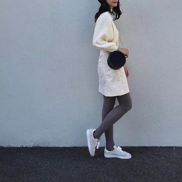 白ニット×白スカート×グレーレギンス×ベージュスニーカーのコーデ画像
