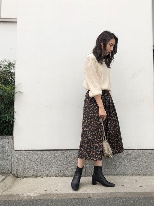 ベージュニット×黒花柄スカート×レザーブーツのコーデ画像