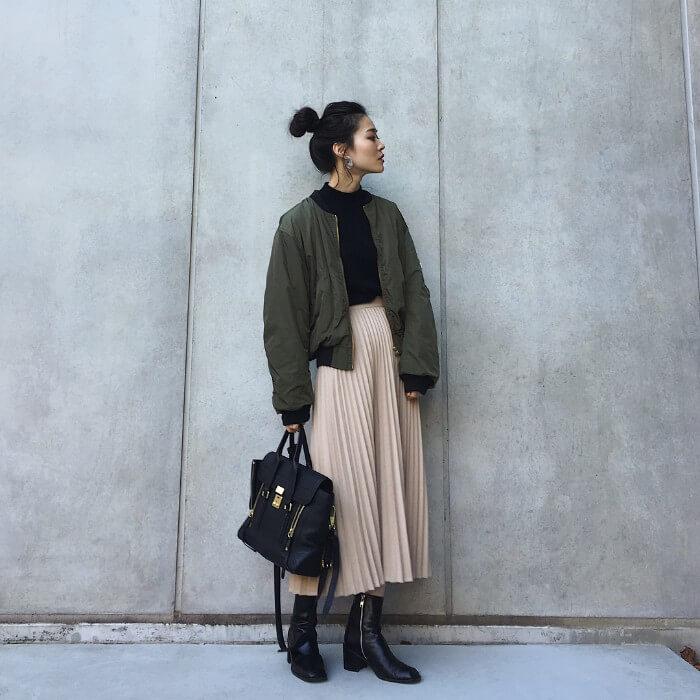 カーキブルゾン×黒インナー×ベージュプリーツスカートのコーデ画像