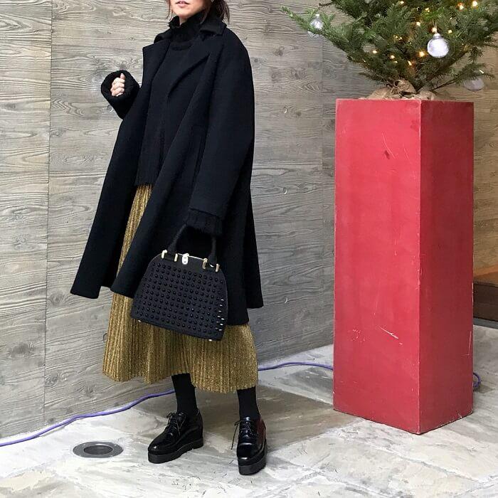イエロースカート×黒コートのコーデ画像