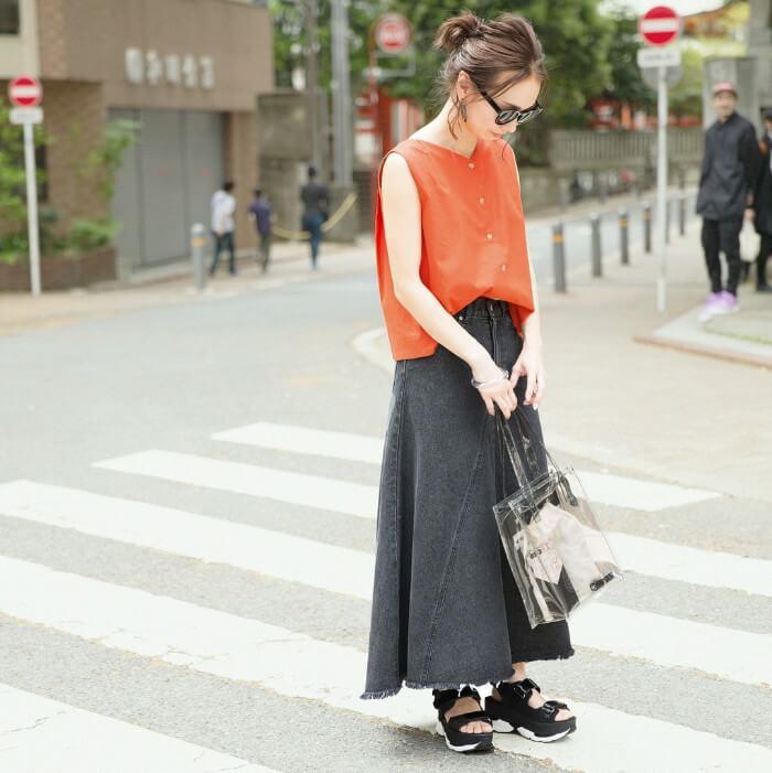濃いグレーのロングスカート×オレンジトップスのコーデ画像