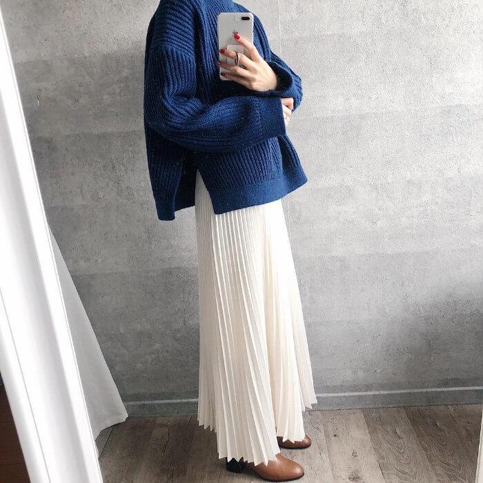 ダークブルー ざっくりニット×ホワイト プリーツスカートのコーデ画像