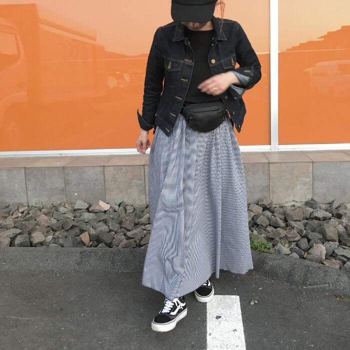 マキシ丈のグレーフレアスカートと黒スニーカーのコーデ画像