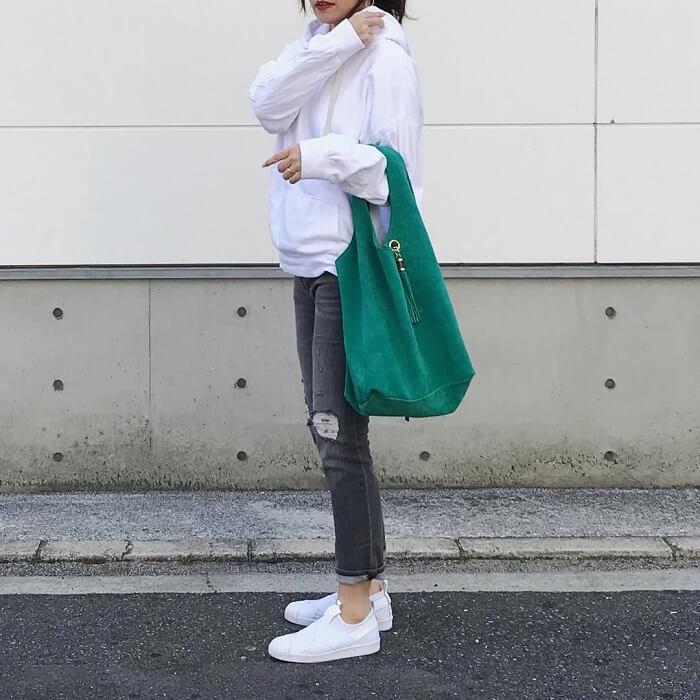 白スウェットパーカー×スキニーデニム×グリーンバッグのコーデ画像