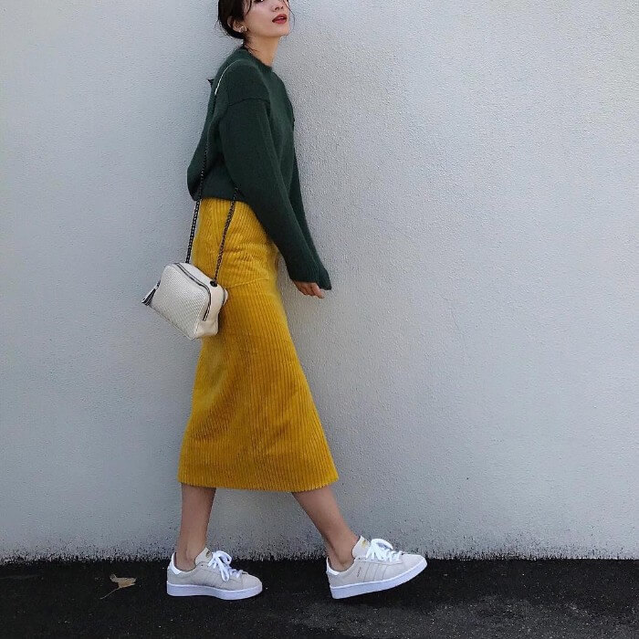 グリーンニット×イエローコーデュロイタイトスカート×白小物のコーデ画像