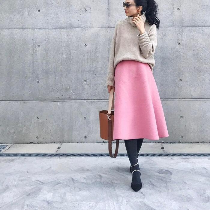 くすみピンク色フレアスカート×ベージュニット×黒タイツのコーデ画像
