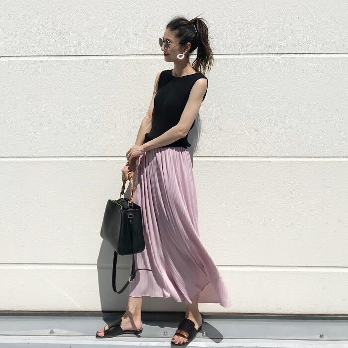くすみピンク色プリーツスカート×黒トップス×モードサンダルのコーデ画像