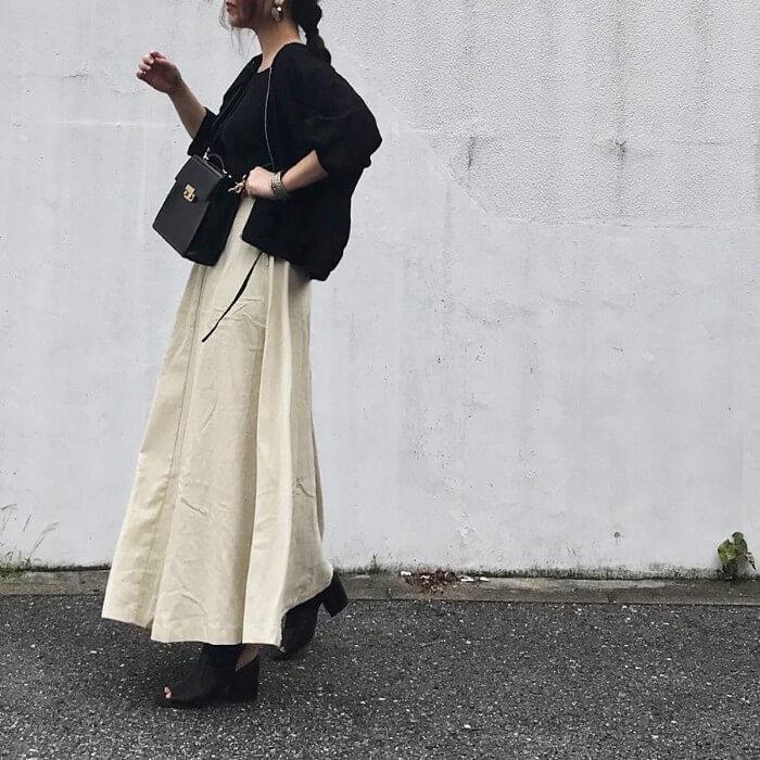 アイボリーコーデュロイスカートと黒トップスのコーデ画像